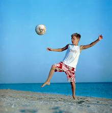 Kind beim Beachsoccer spielen